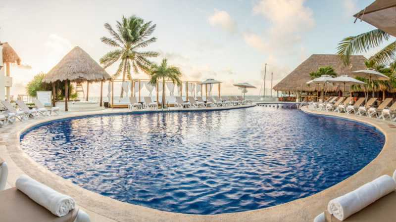 Ground level view of the main pool at Desire Resort and Spa Riviera Maya